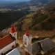 Up Top Drone Shot of a Beautiful Slovenian Church Surrounded By Hills Full of Trees and Small City - VideoHive Item for Sale