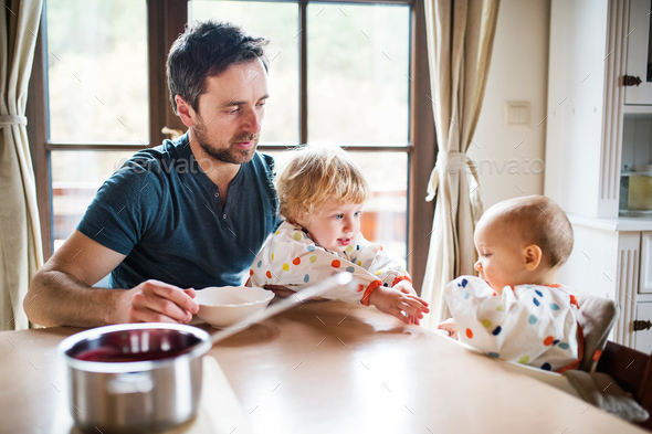Father feeding two toddlers at home. - Stock Photo - Images