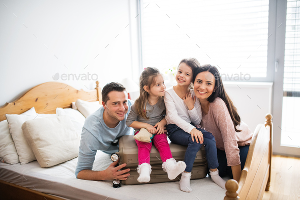 Young family with two children packing for holiday. - Stock Photo - Images