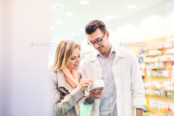 Male pharmacist serving a female customer. - Stock Photo - Images