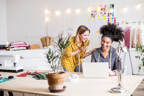 Young creative women with laptop in studio, startup business. - Stock Photo - Images