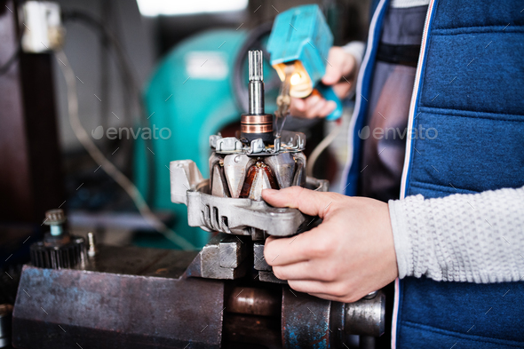 Man mechanic repairing a car in a garage. - Stock Photo - Images
