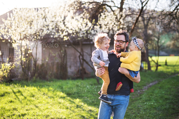 A father with toddler children outside in spring nature. - Stock Photo - Images