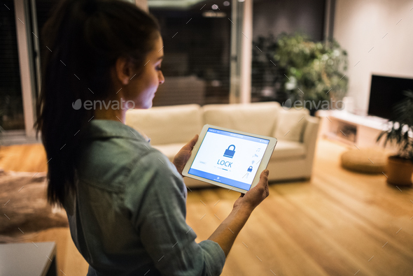 A woman holding a tablet with smart home screen. - Stock Photo - Images