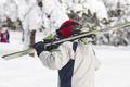 Skier carrying skis on a snowy forest landscape. Winter sport - PhotoDune Item for Sale