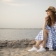 Attractive Woman in Hat and Dress Is Sitting and Looking at Sunset - VideoHive Item for Sale