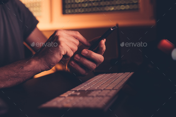 Man with smart phone in home office interior - Stock Photo - Images