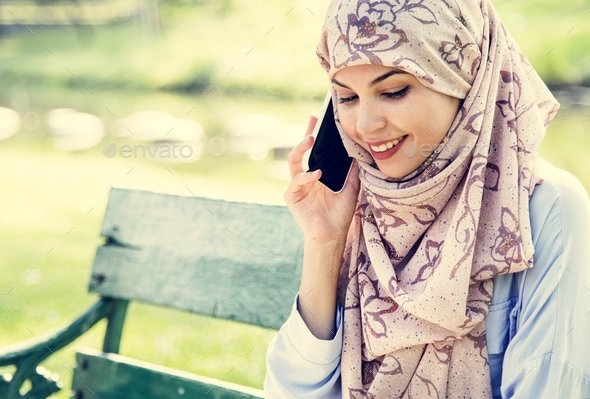 Islamic woman using mobile phone with smiling at park - Stock Photo - Images