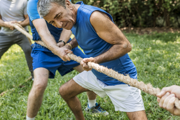 Mature people in tug of war - Stock Photo - Images