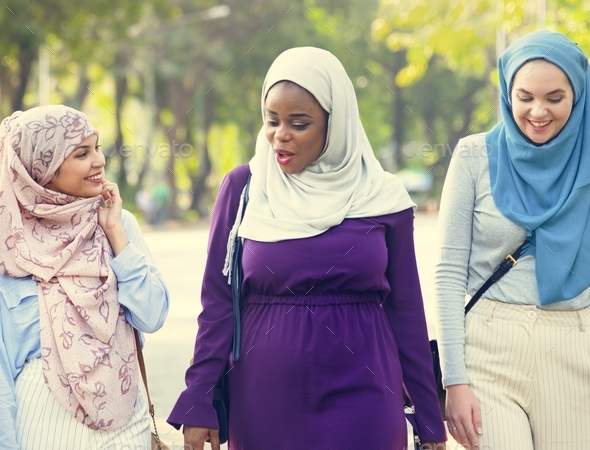 Islamic women friends walking and discussing together - Stock Photo - Images
