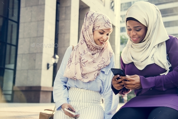 Islamic friends looking at the phone and smiling - Stock Photo - Images