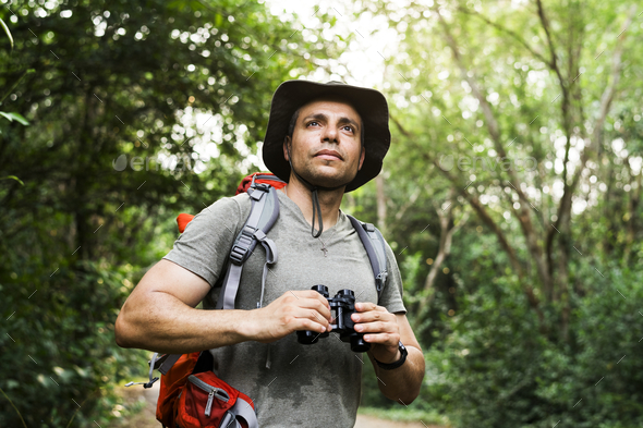Man holding binoculars in the forest - Stock Photo - Images