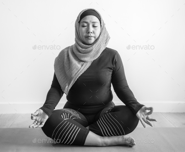 Islamic woman doing yoga in the room - Stock Photo - Images