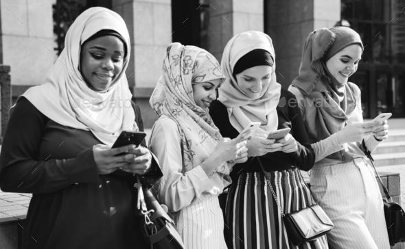 Group of islamic girls using smart phone - Stock Photo - Images