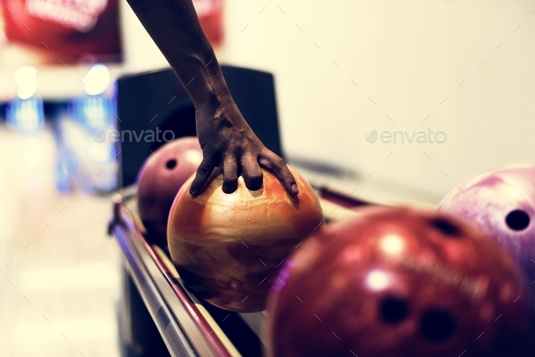 African American boy picking up a bowling ball hobby and leisure concept - Stock Photo - Images