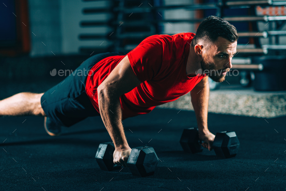 Cross training. Young man exercising with dumbbells - Stock Photo - Images