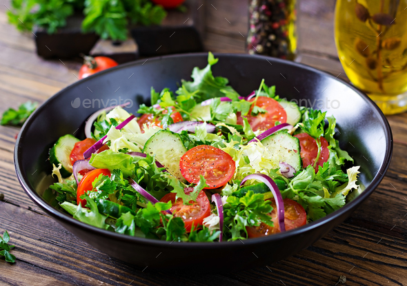 Salad from tomatoes, cucumber, red onions and lettuce leaves.  - Stock Photo - Images