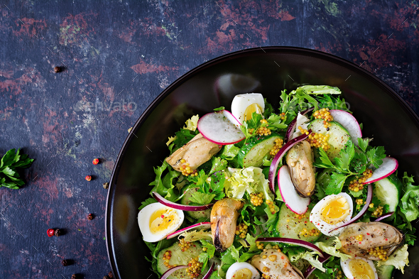 Dietary salad with mussels, quail eggs, cucumbers, radish and lettuce - Stock Photo - Images