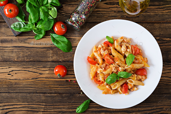 Penne pasta in tomato sauce with chicken, tomatoes, decorated with basil on a wooden table - Stock Photo - Images