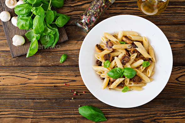 Vegetarian Vegetable pasta penne  with mushrooms  in white bowl on wooden table.  - Stock Photo - Images
