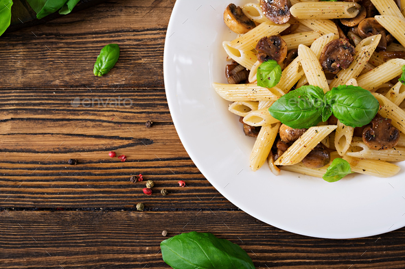 Vegetarian Vegetable pasta penne  with mushrooms  in white bowl on wooden table - Stock Photo - Images