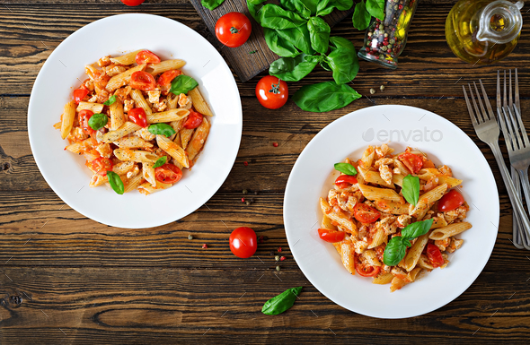 Penne pasta in tomato sauce with chicken, tomatoes, decorated with basil on a wooden table. - Stock Photo - Images