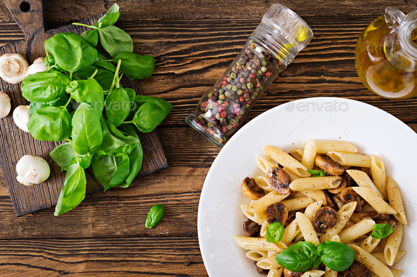 Vegetarian Vegetable pasta penne  with mushrooms  in white bowl on wooden table. Vegan food. - Stock Photo - Images