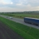 Aerial Shot of Truck Driving a Road Between Fields - VideoHive Item for Sale