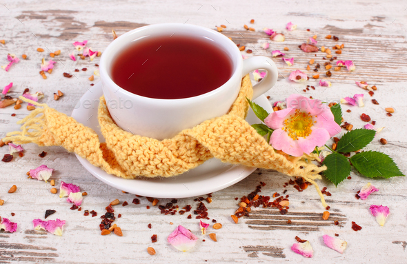 Cup of tea with wild rose flower on old rustic board - Stock Photo - Images
