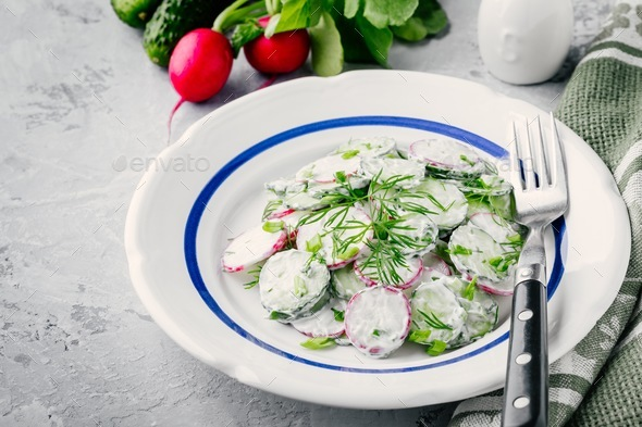 Summer salad with radish and cucumber, green onion and dill with sour cream dressing - Stock Photo - Images