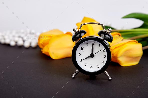 Black alarm clock near bouquet yellow tulips - Stock Photo - Images
