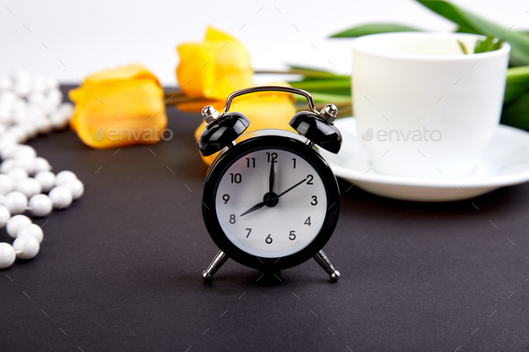 Black alarm clock near bouquet yellow tulips - Stock Photo - Images