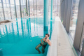 Man talking on cell phone inside the swimming pool at luxury hotel - PhotoDune Item for Sale