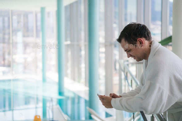 Happy guy communicating on telephone in luxury spa hotel - Stock Photo - Images