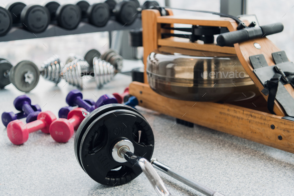 Weight plates and dumbbells on floor in gym, close up - Stock Photo - Images