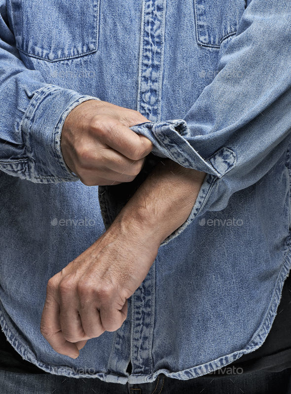 Man in denim shirt rolling up his sleeves - Stock Photo - Images