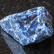 raw Sodalite gemstone on black granite - PhotoDune Item for Sale