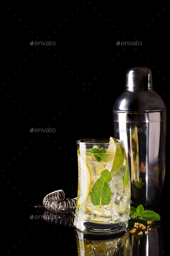 Glass of a cold cocktail drink with tonic served with brown sugar and shaker - Stock Photo - Images
