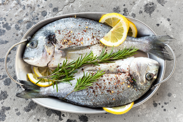 Fresh fish dorado. Raw dorado fish with lemon and rosemary. Sea bream or dorada fish - Stock Photo - Images