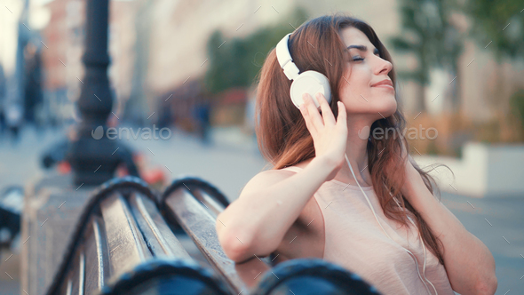 Young girl with headphones outdoors - Stock Photo - Images