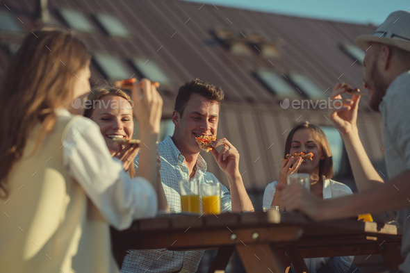 Young friends eating pizza outdoors - Stock Photo - Images