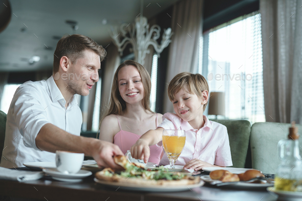 Young family in a restaurant - Stock Photo - Images