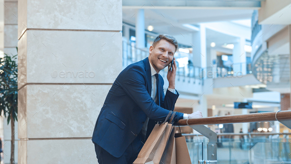 Young smiling businessman with shopping bags - Stock Photo - Images