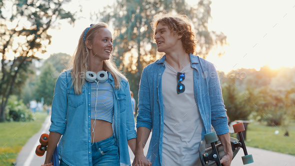 Young smiling couple with skateboards - Stock Photo - Images