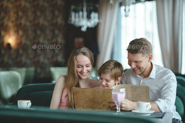 Smiling family in a restaurant - Stock Photo - Images