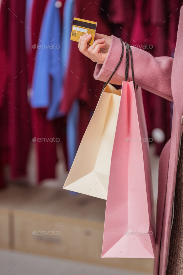 Young girl with a credit card and shopping bags - Stock Photo - Images