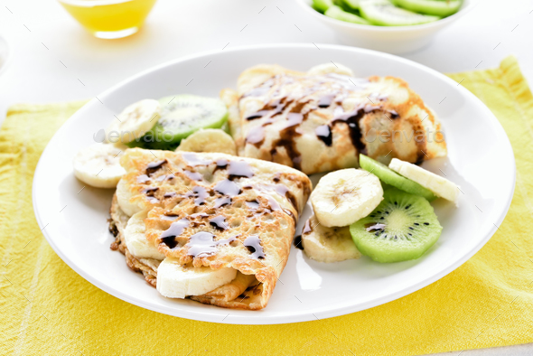 Crepes with banana, kiwi slices and chocolate sauce - Stock Photo - Images
