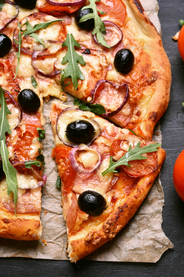 Sliced pizza with tomato, salami and olives - Stock Photo - Images
