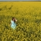 Beautiful Brunette Wearing Blue Dress Stand Among Yellow Flowers on the Field - VideoHive Item for Sale