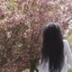 Woman in White Dress Walks Near the Blooming Sakura Trees in - VideoHive Item for Sale